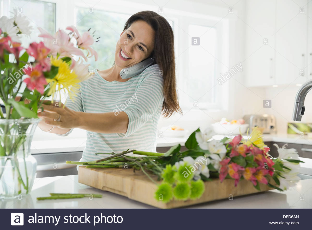 Woman talking on phone in kitchen while arranging flowers - Stock Image