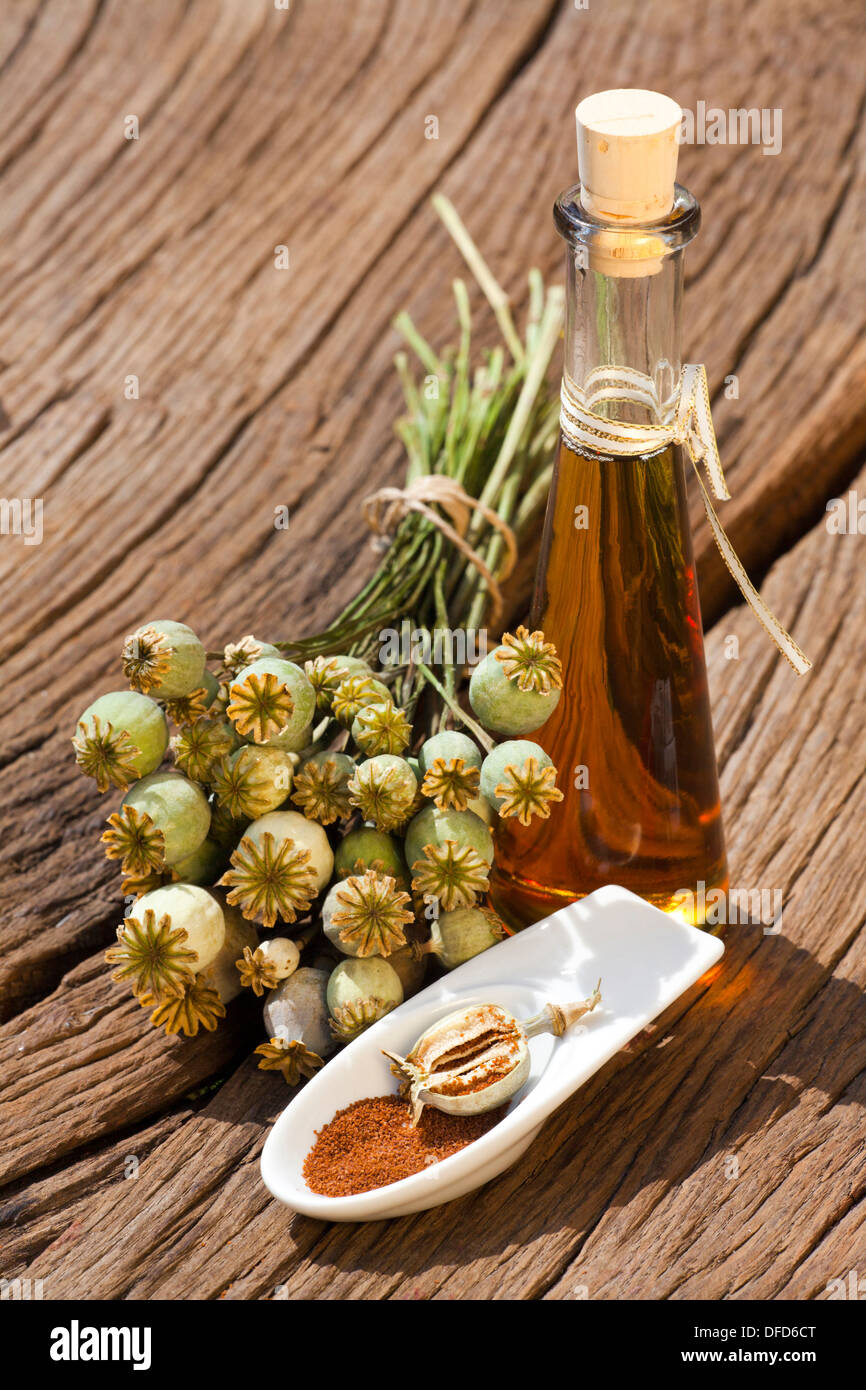 Poppy capsule, poppy seeds and poppy seed oil bottle is standing on an old rustic wooden table - Stock Image