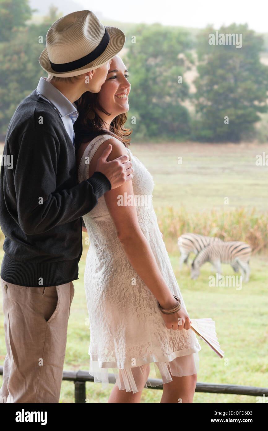 Couple in late twenties on honeymoon watching zebras in pasture, Winelands, Western Cape, Stellenbosch, South Africa - Stock Image