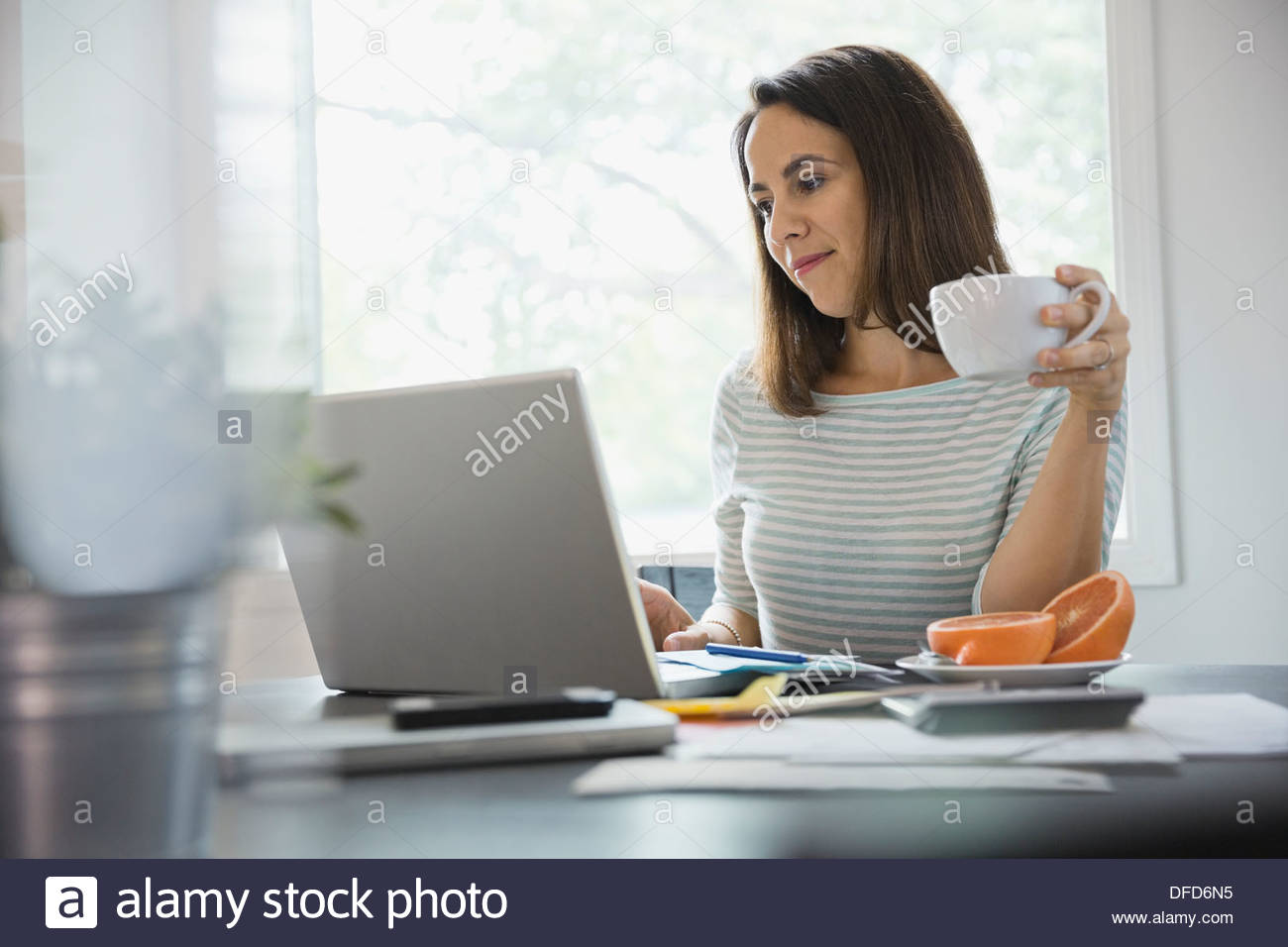 Woman working on laptop at home office - Stock Image