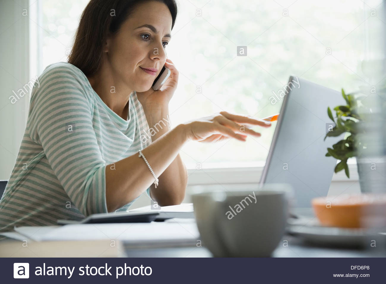 Businesswoman using technologies at desk in home office - Stock Image