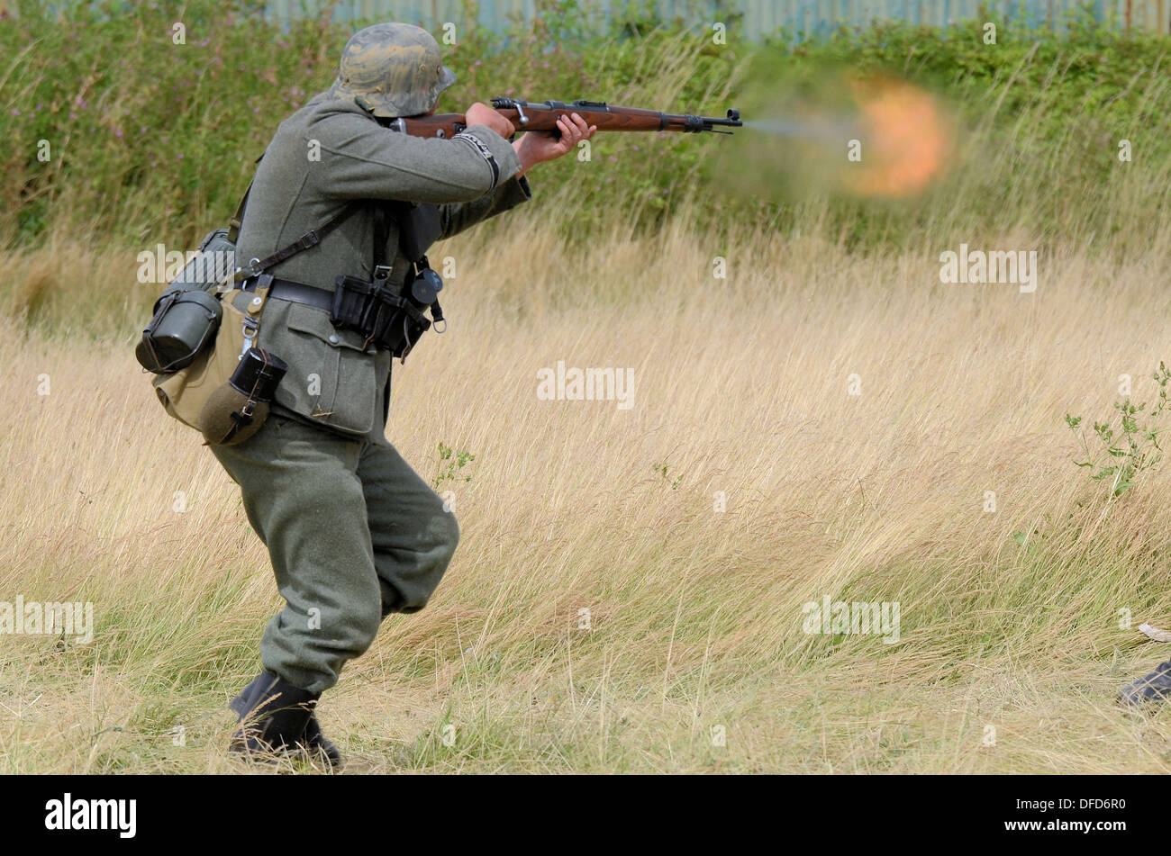 A World War II re-enactor in German army uniform fires his rifle - Stock Image