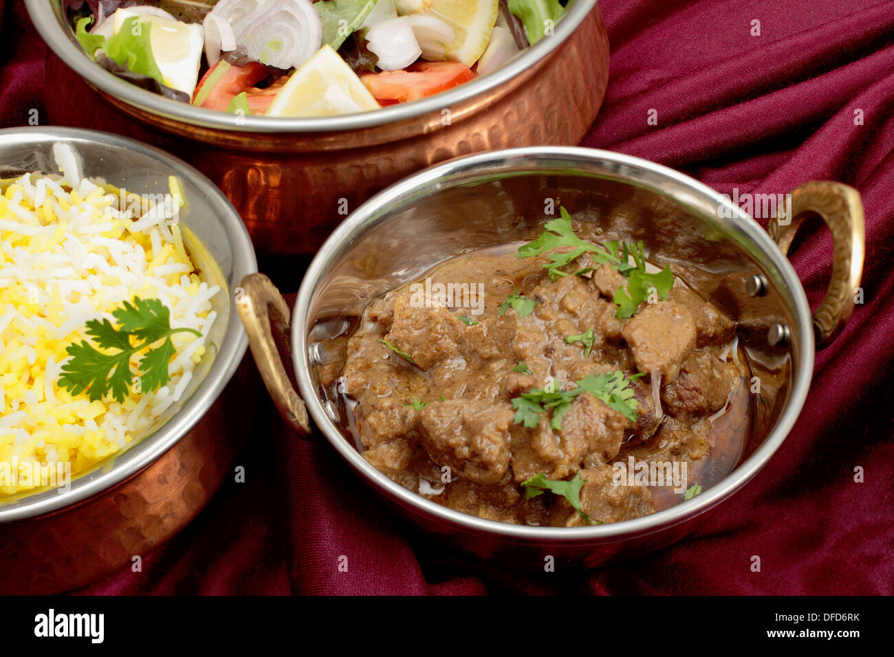 Indian copper dishes with beef rogan josh, white and yellow rice and a salad, - Stock Image