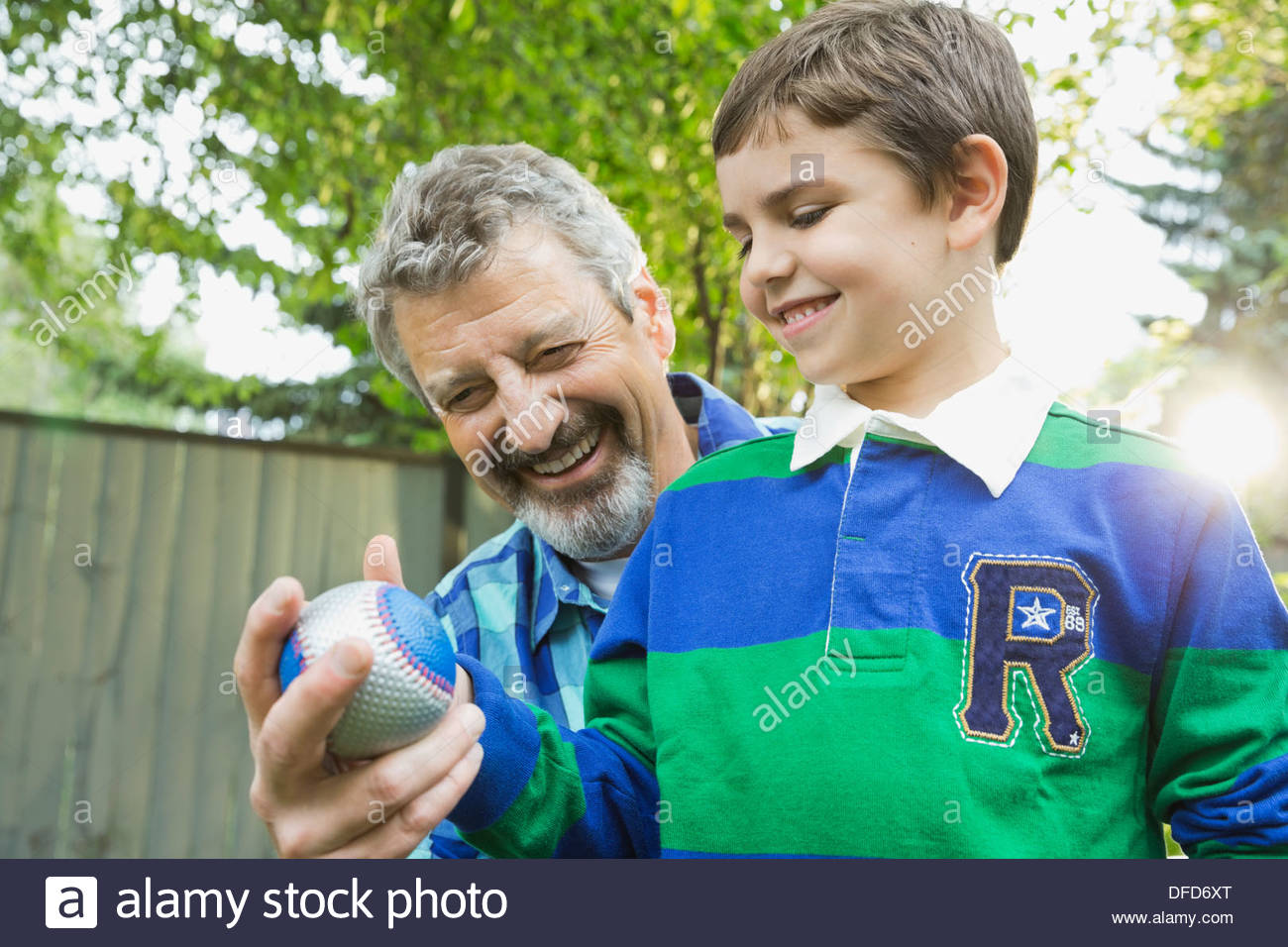 Grandfather teaching grandson how to throw a baseball - Stock Image