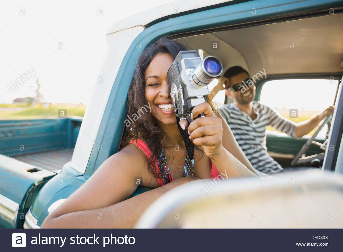 Woman looking through vintage camera in pick-up truck - Stock Image