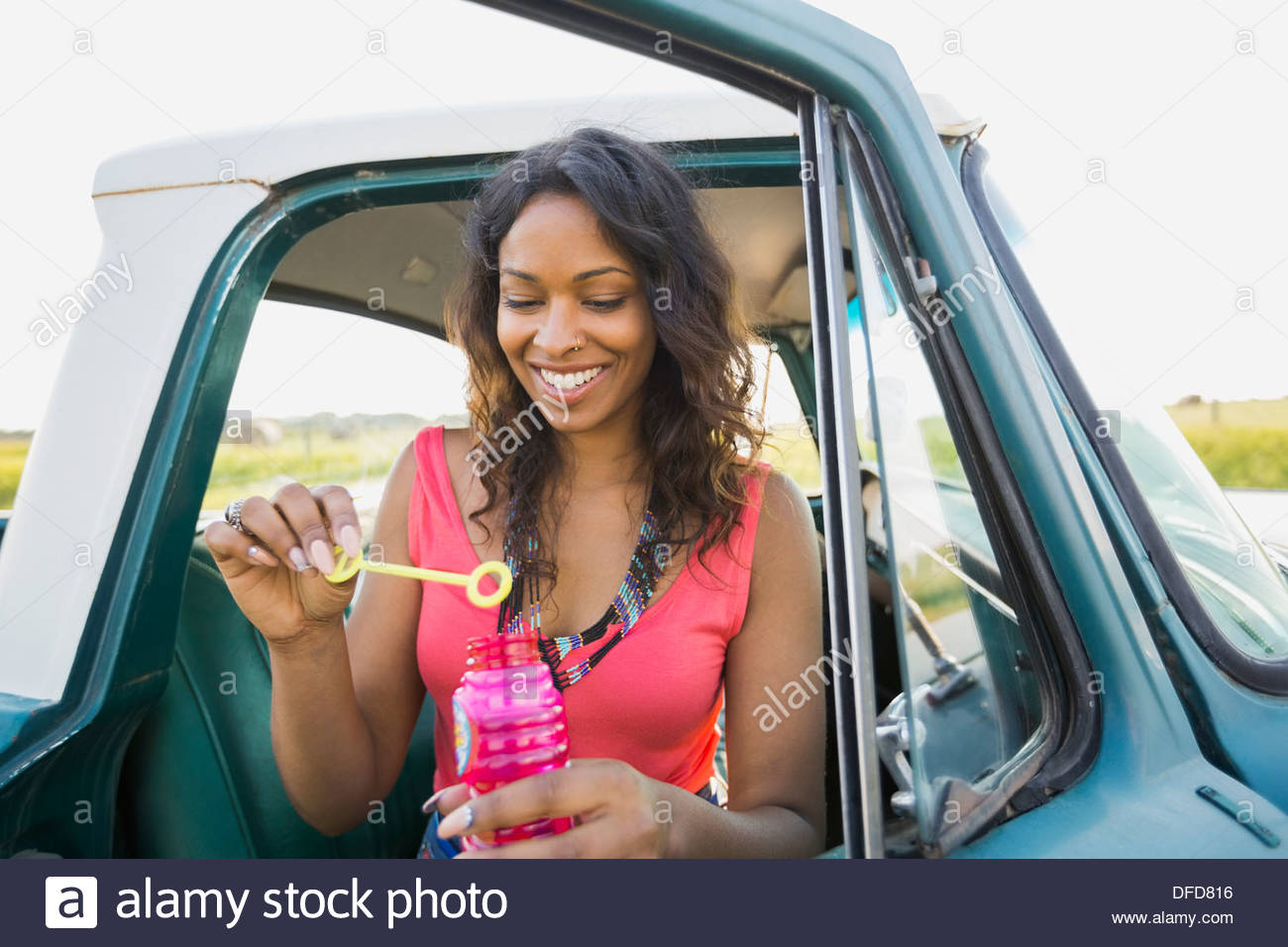 Woman blowing bubbles out of pick-up truck - Stock Image