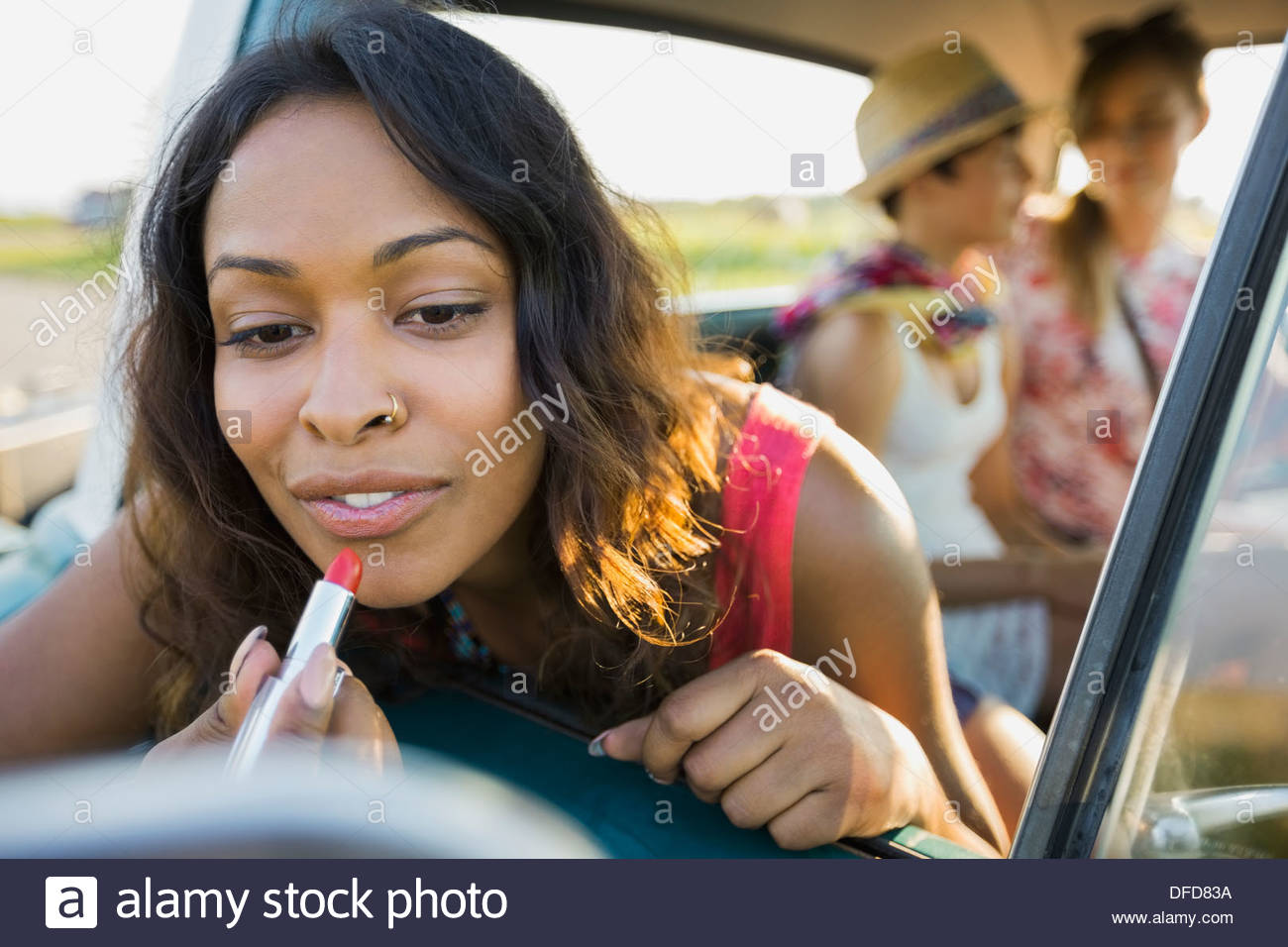 Woman applying lipstick in rear view mirror - Stock Image