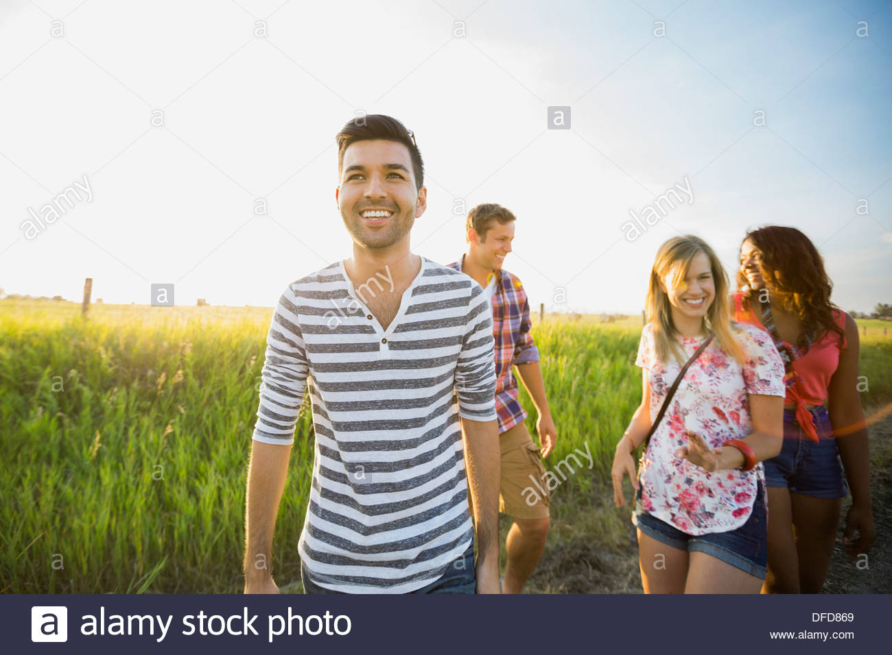 Friends walking along country road - Stock Image