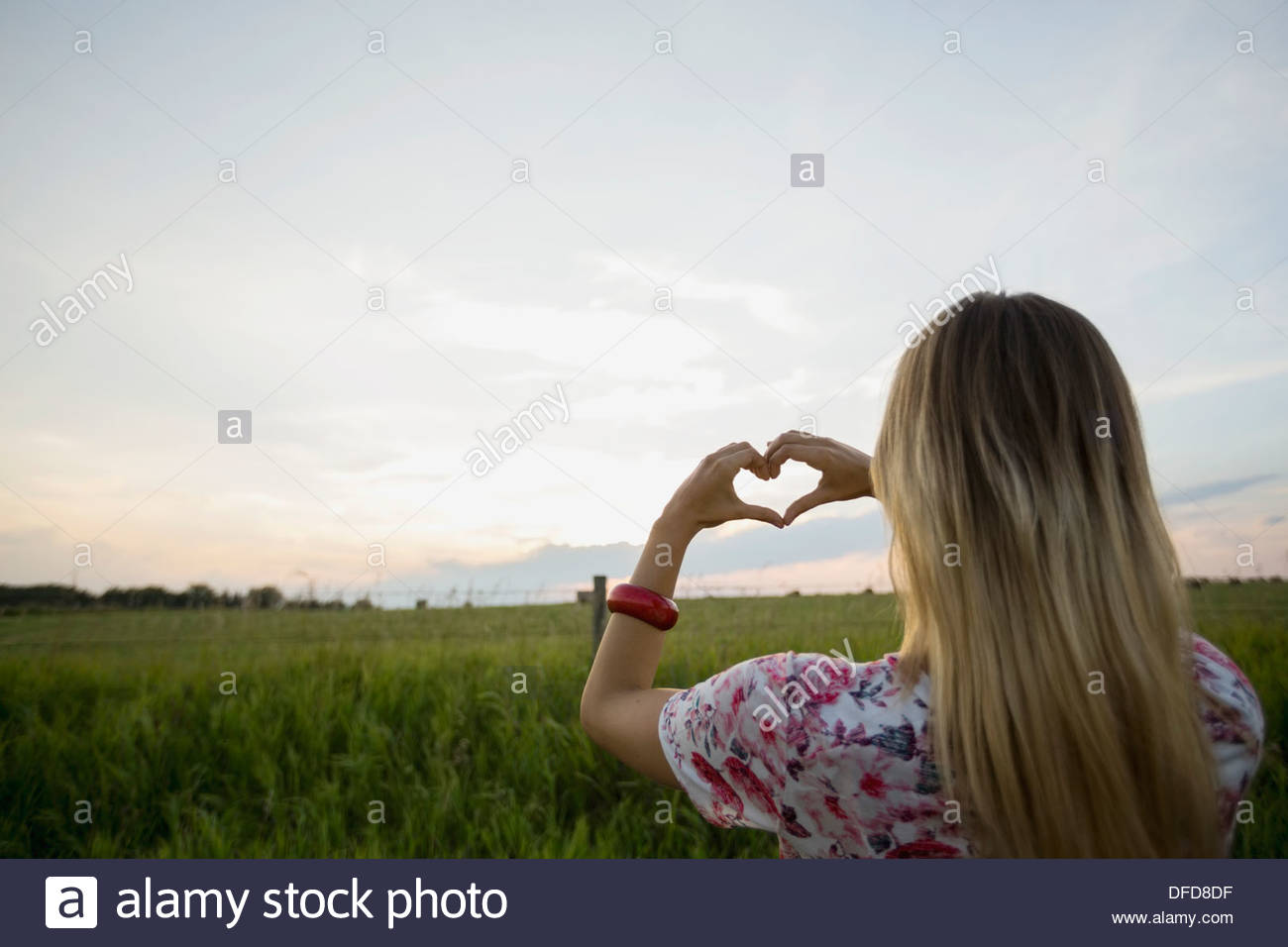 Rear view of woman framing heart with hands against sky - Stock Image
