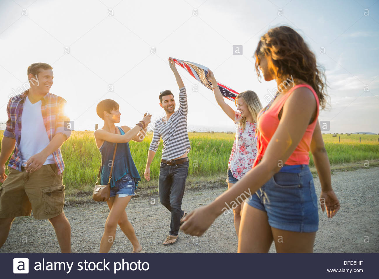 Friends holding up an American flag outdoors - Stock Image