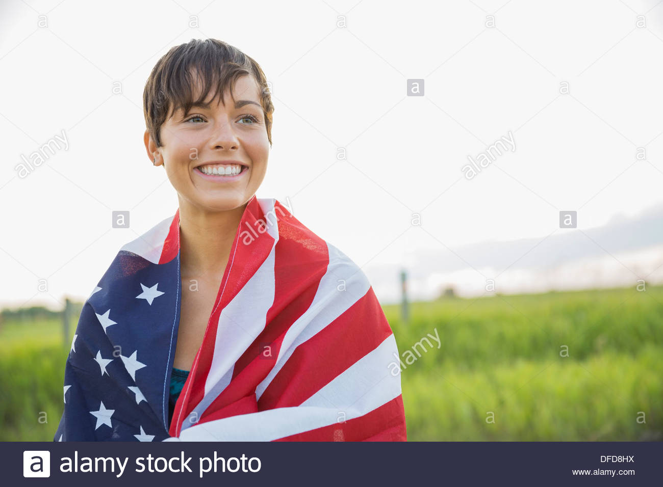 Young woman wrapped in American flag - Stock Image