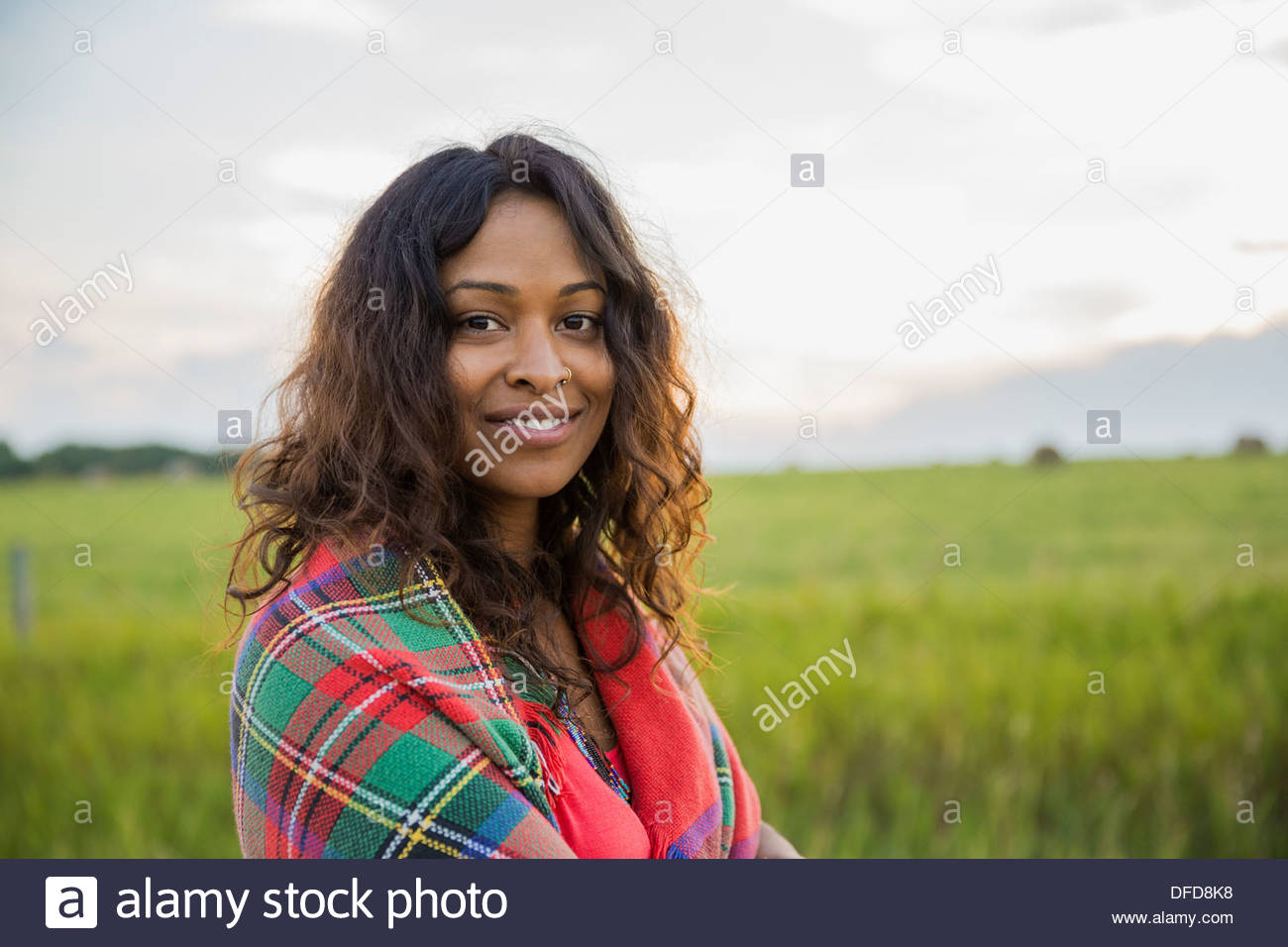 Portrait of smiling woman wrapped in blanket outdoors - Stock Image