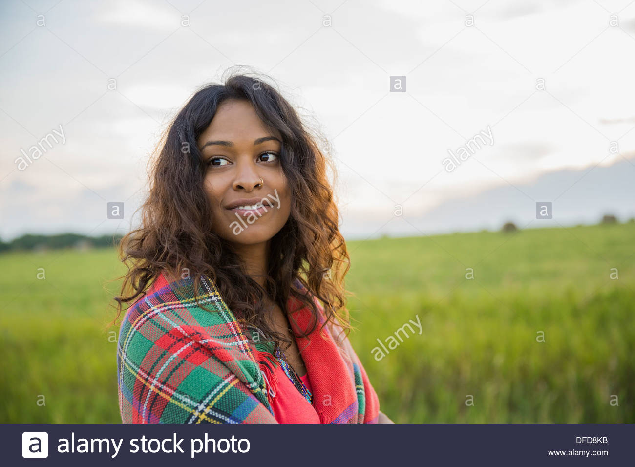 Smiling woman wrapped in blanket outdoors - Stock Image