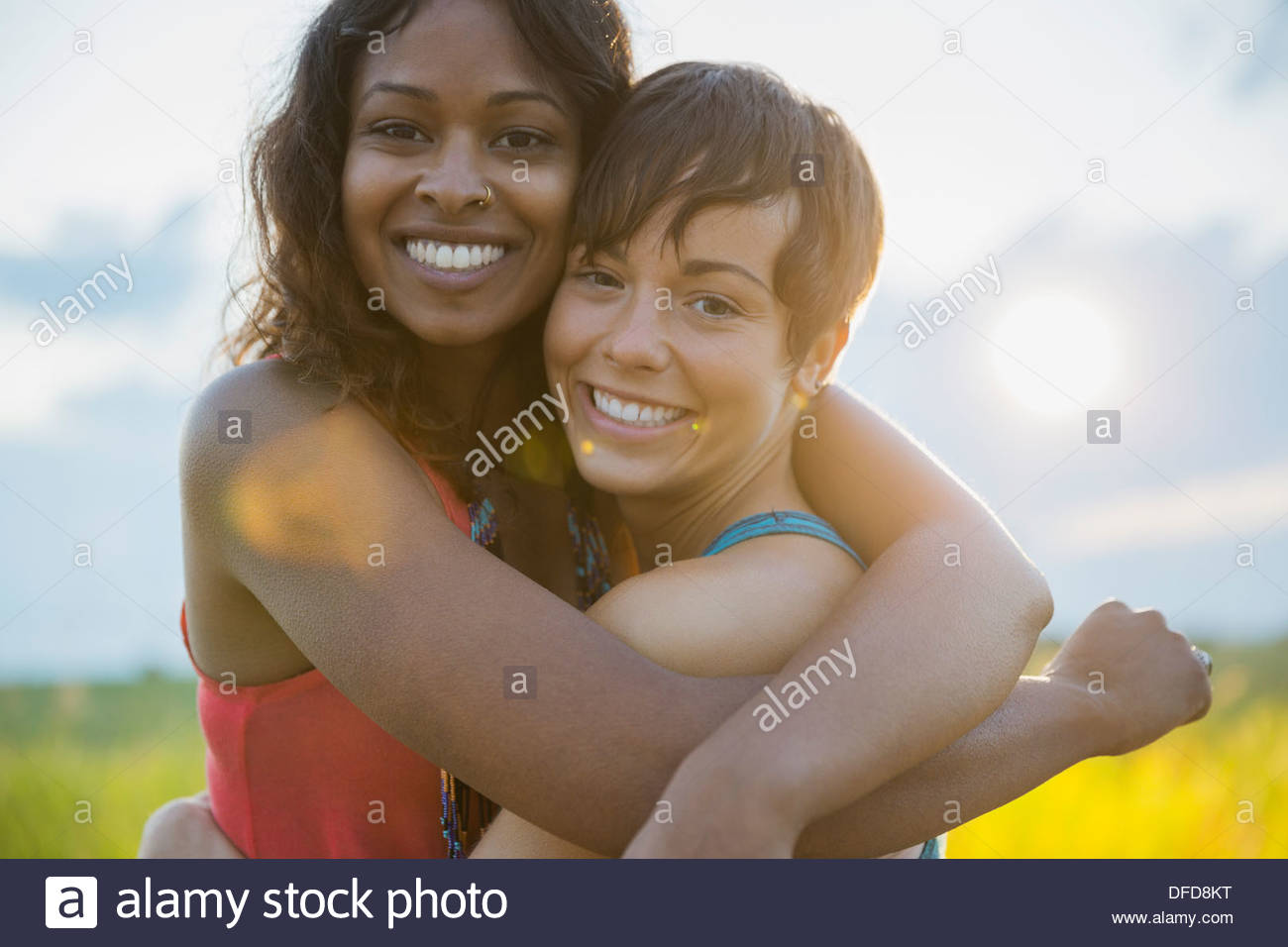 Portrait of young women embracing outdoors - Stock Image
