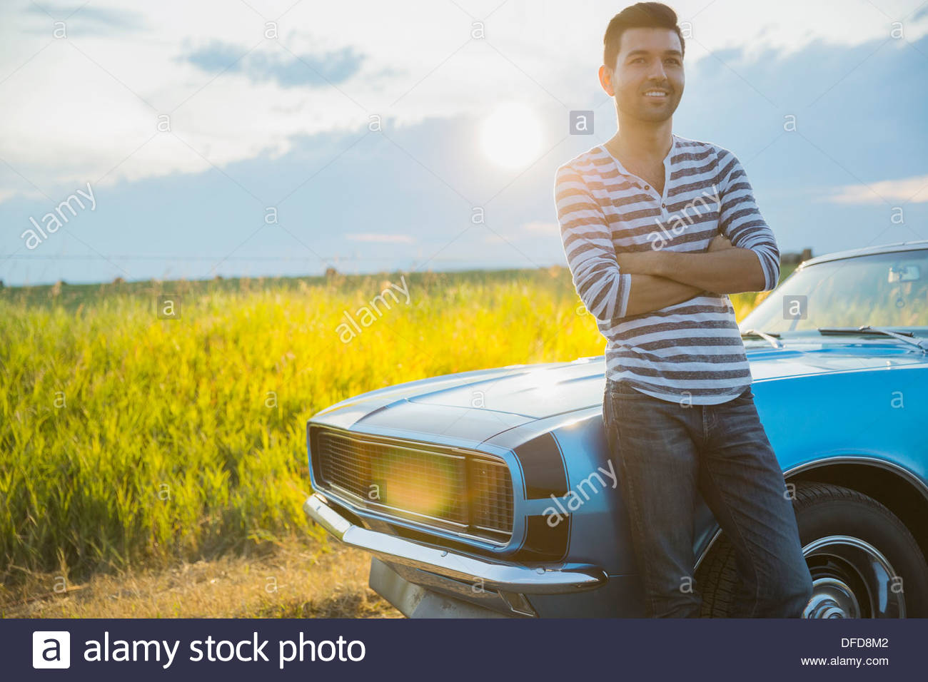Smiling man leaning against convertible - Stock Image