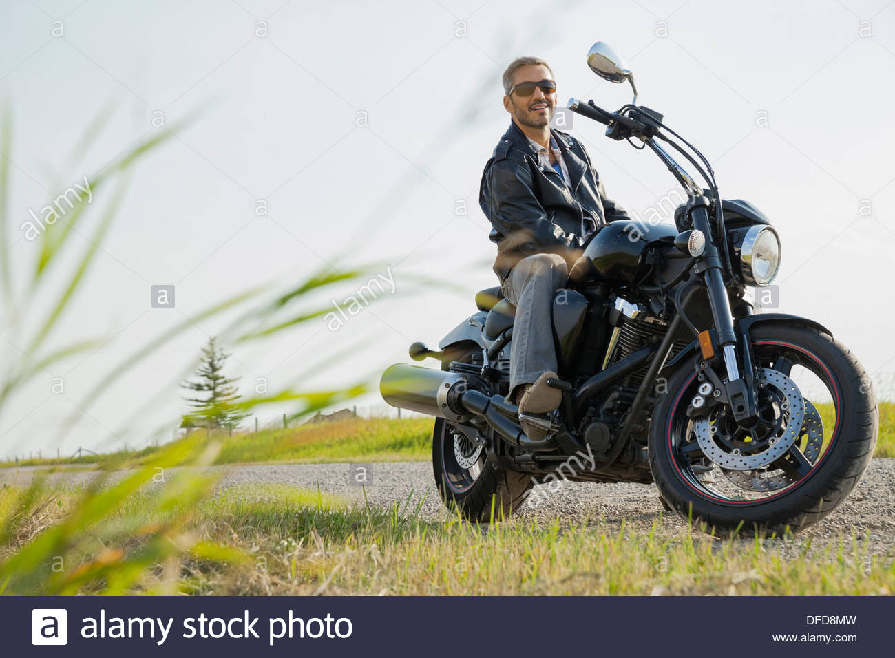 Portrait of biker sitting on motorcycle in the country - Stock Image