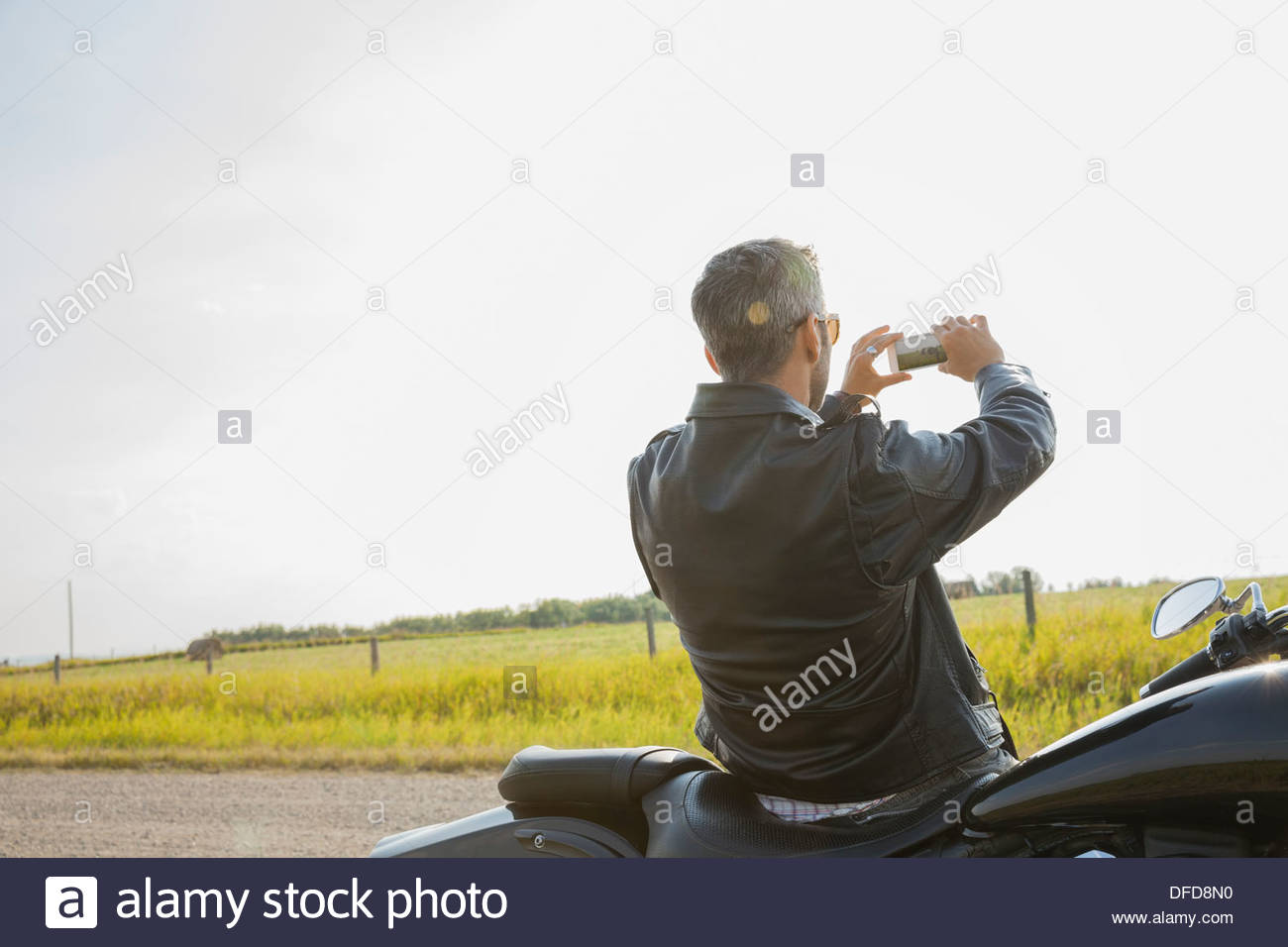 Rear view of biker photographing field during road trip - Stock Image