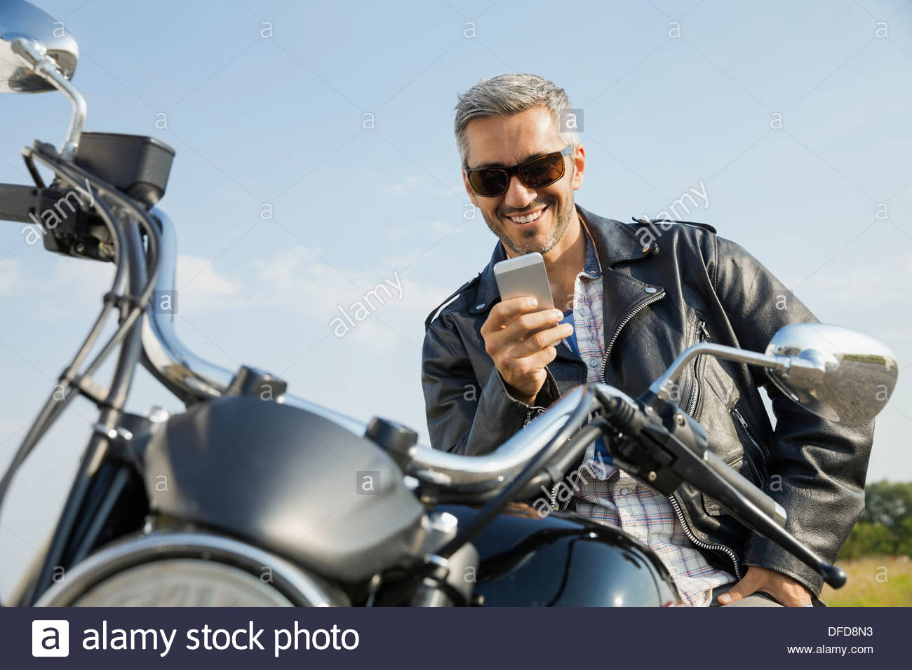 Man sitting on motorcycle and reading smart phone Stock Photo