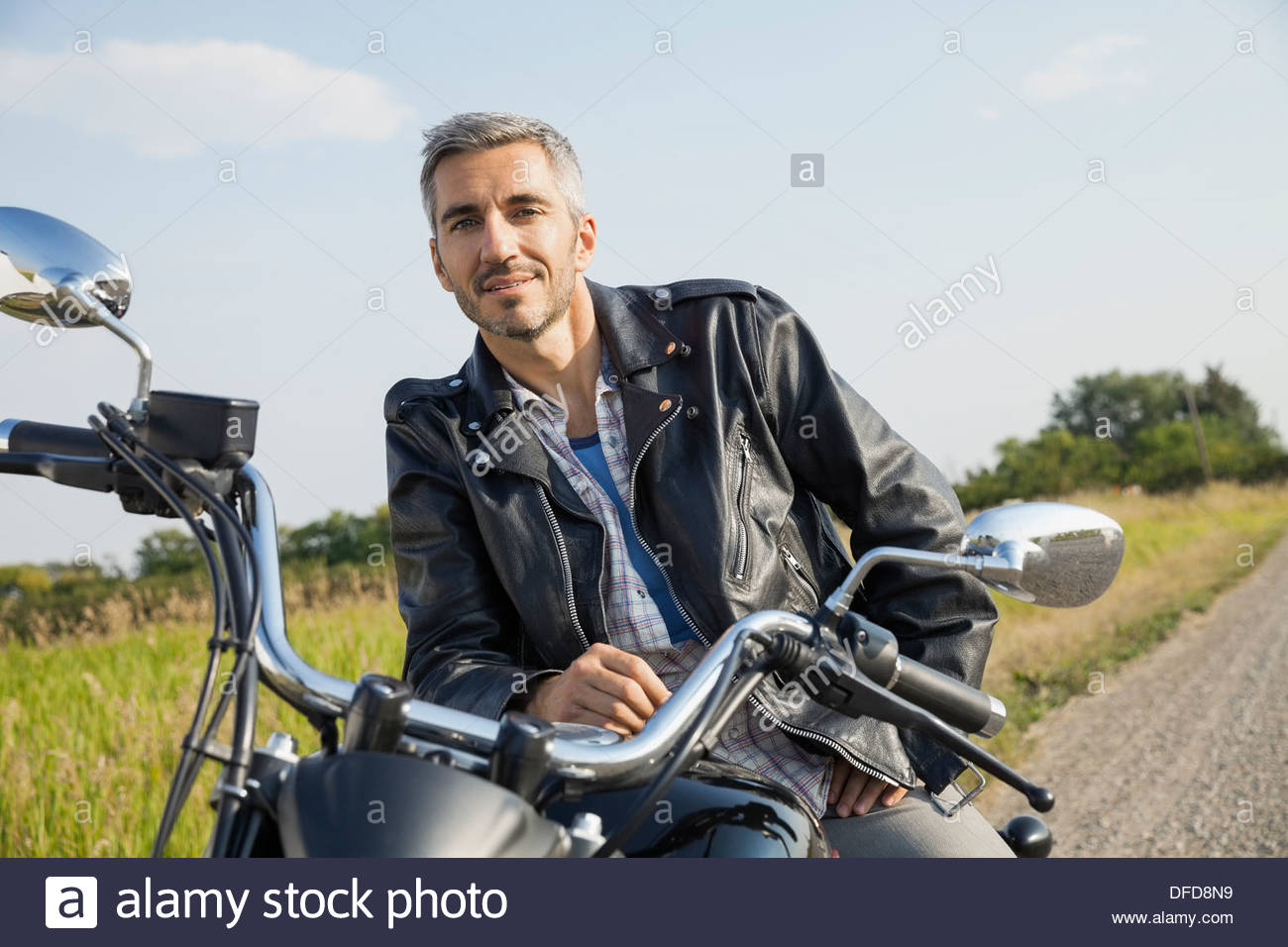 Portrait of confident biker sitting on motorcycle - Stock Image