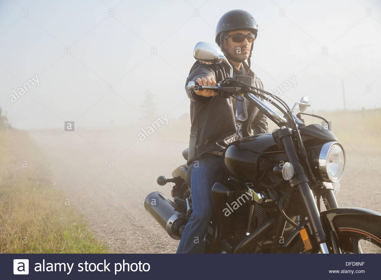 Male biker taking a break on country road - Stock Image