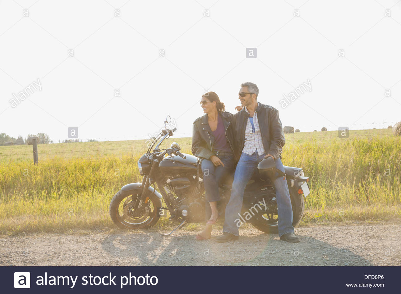 Happy couple with motorcycle taking a break - Stock Image
