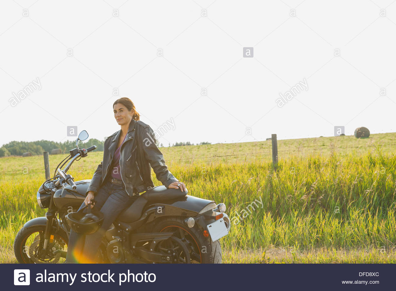 Thoughtful female biker leaning against motorcycle - Stock Image