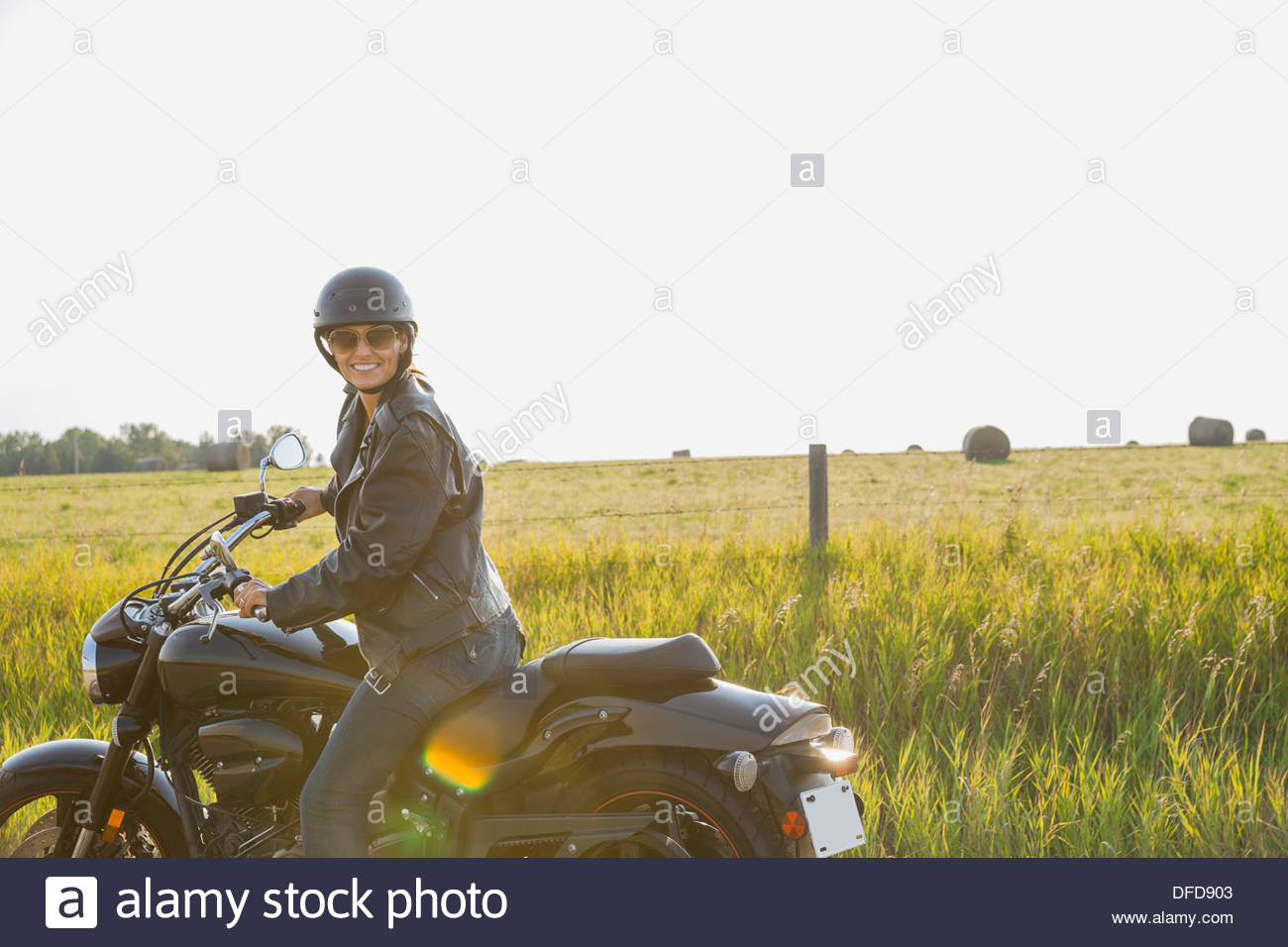 Portrait of female biker sitting on motorcycle - Stock Image