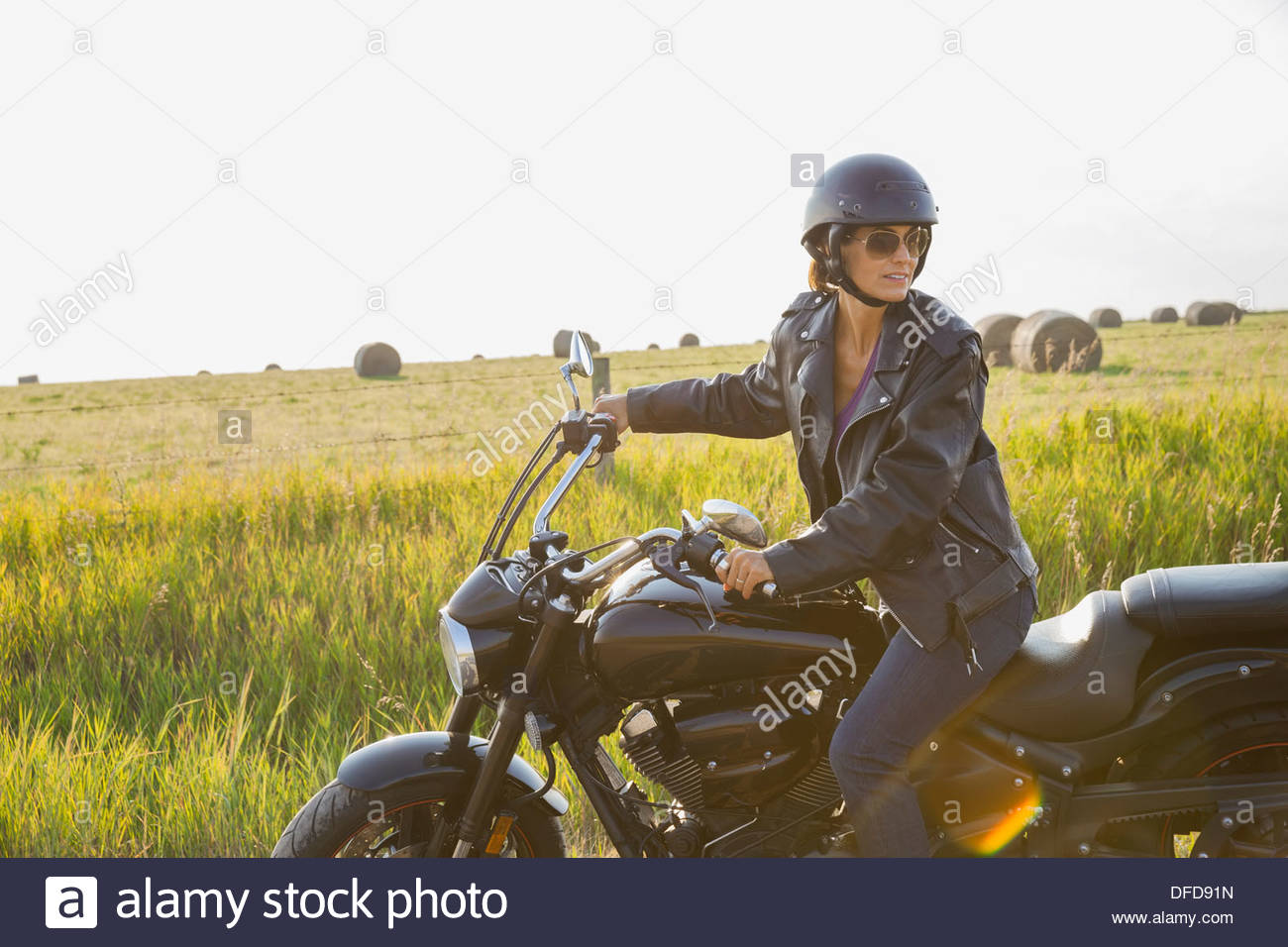 Woman sitting on motorcycle outdoors - Stock Image