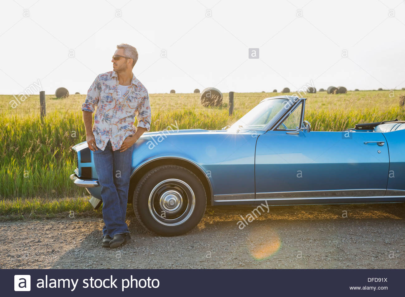 Man leaning against blue convertible - Stock Image