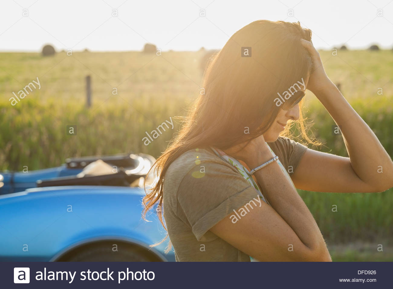 Side view of woman running fingers through hair - Stock Image