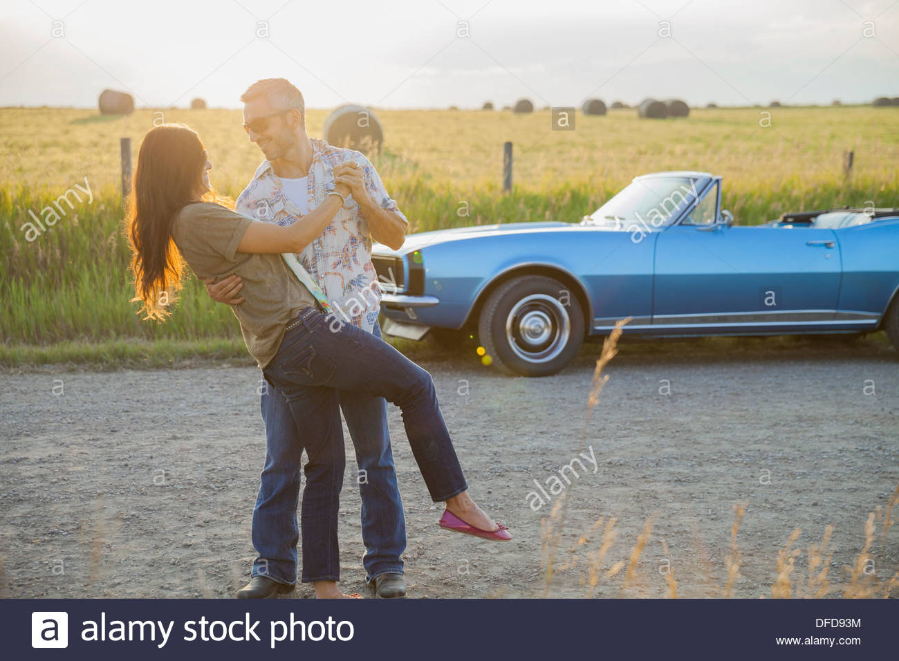 Romantic couple dancing on country road - Stock Image