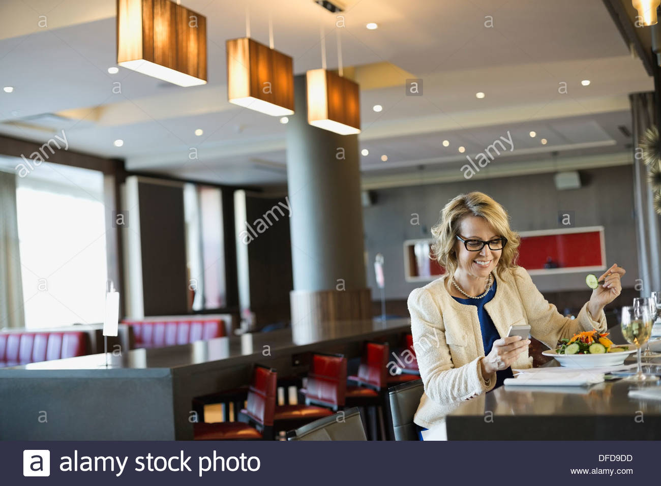 Businesswoman using smart phone while eating in hotel restaurant - Stock Image