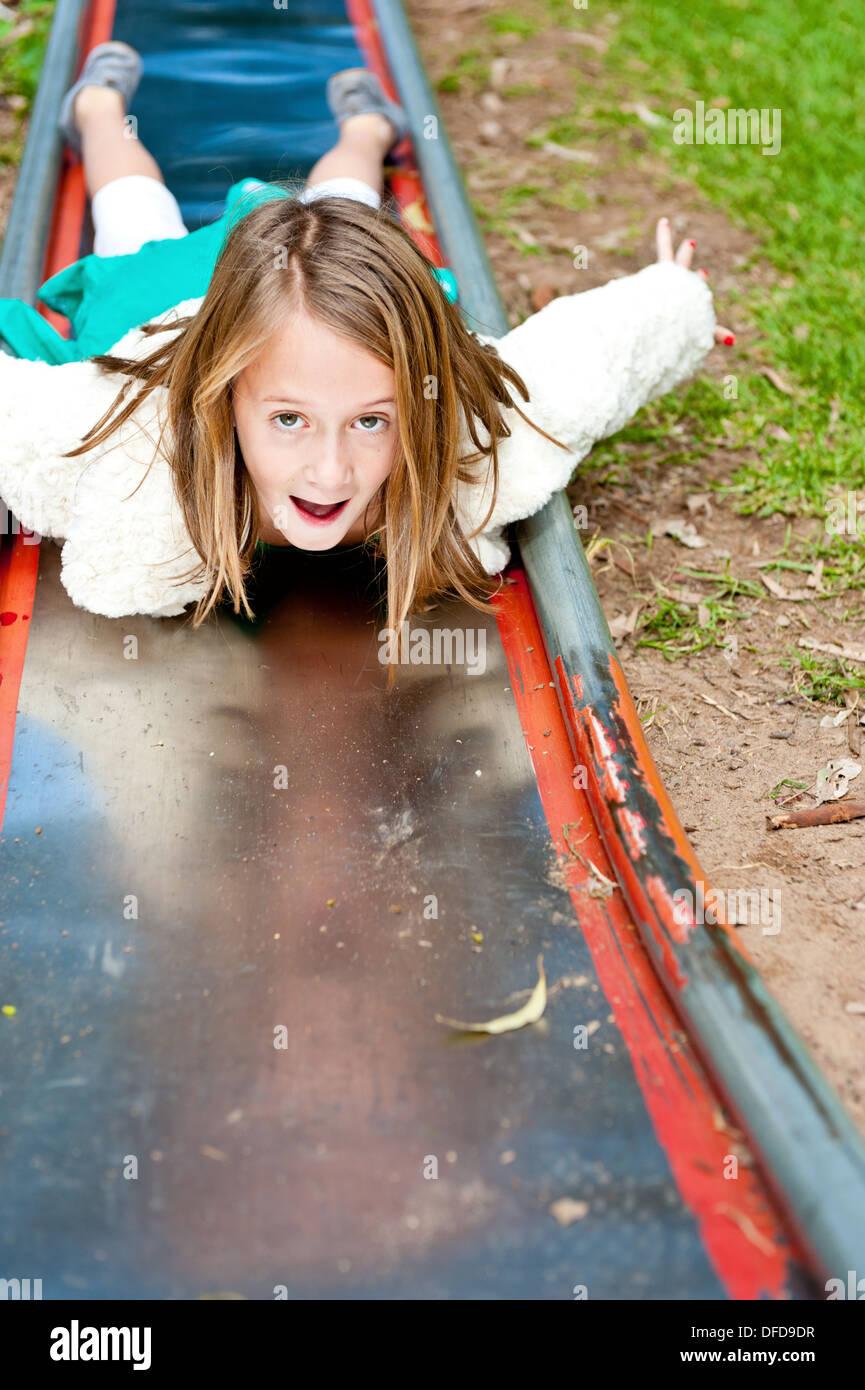 little girl sliding down a slippery slide on her tummy - Stock Image