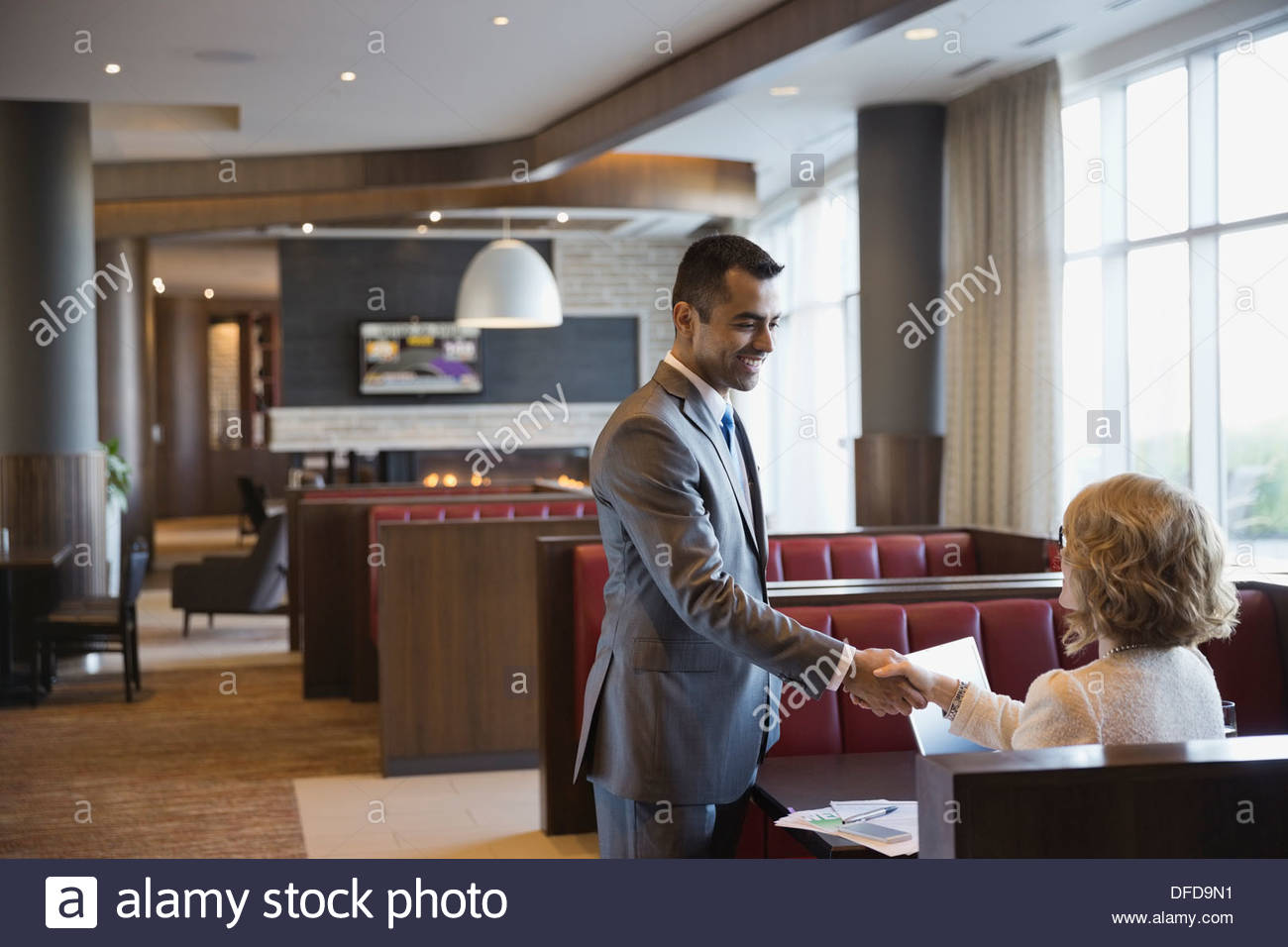 Businessman shaking hands with female colleague in hotel restaurant - Stock Image