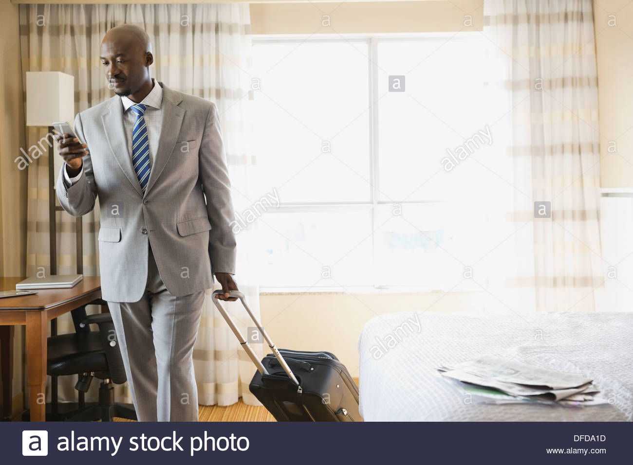 Businessman with luggage checking smart phone - Stock Image
