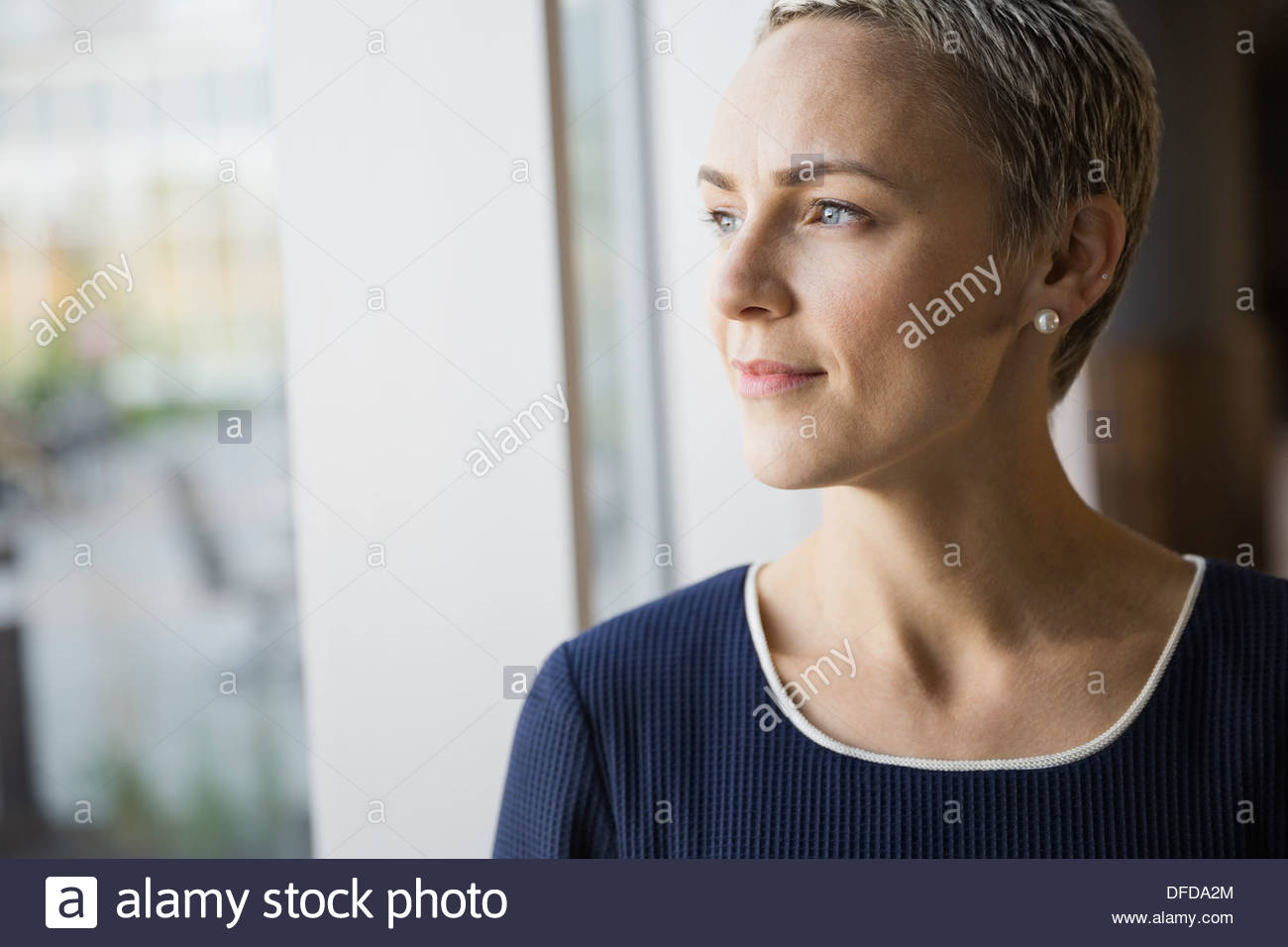 Thoughtful businesswoman looking out window in hotel room - Stock Image