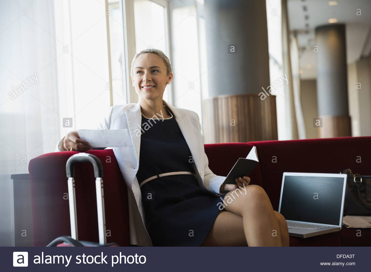Smiling businesswoman relaxing in airport waiting area - Stock Image