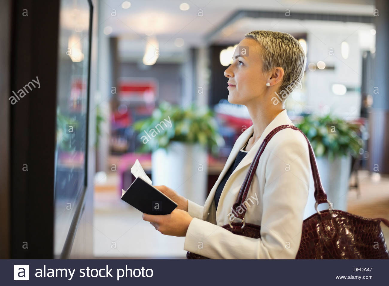 Businesswoman checking schedule at airport terminal - Stock Image
