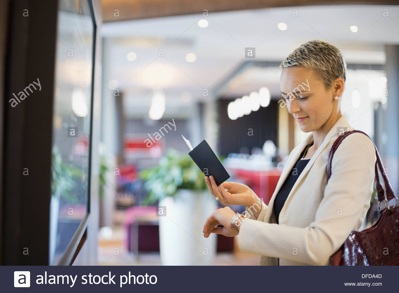 Businesswoman checking the time at airport terminal - Stock Image