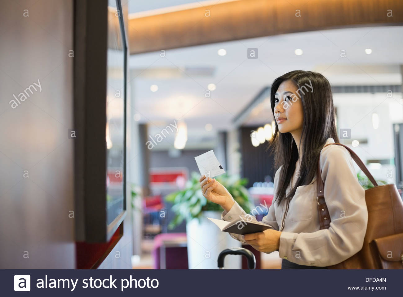 Businesswoman checking schedule at airport - Stock Image