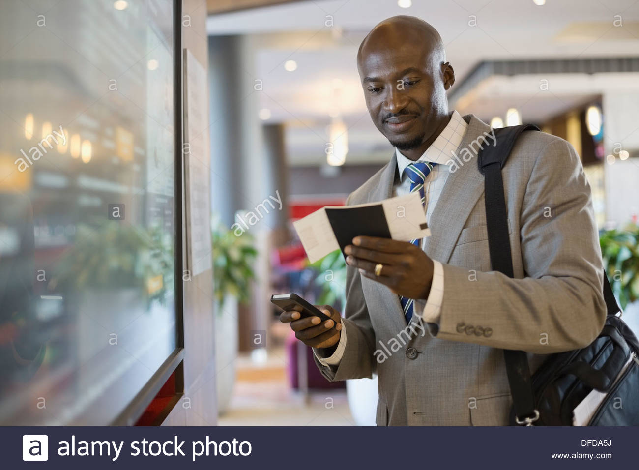 Businessman with smart phone and boarding pass standing in airport terminal - Stock Image