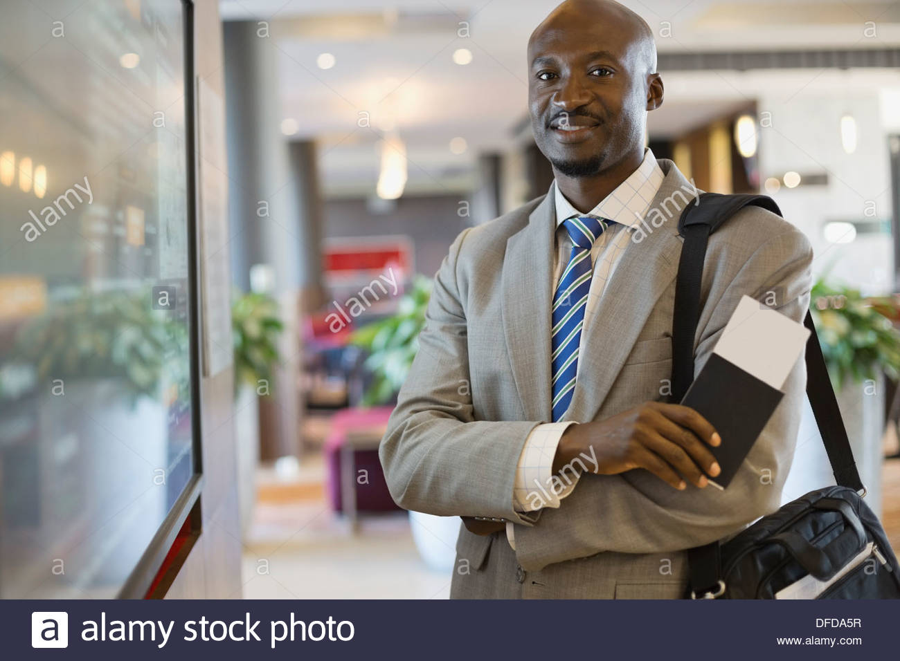 Portrait of confident businessman standing in airport terminal - Stock Image