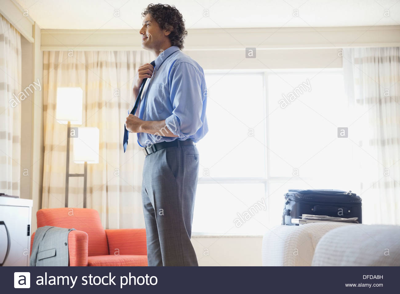 Businessman straightening tie in hotel room - Stock Image