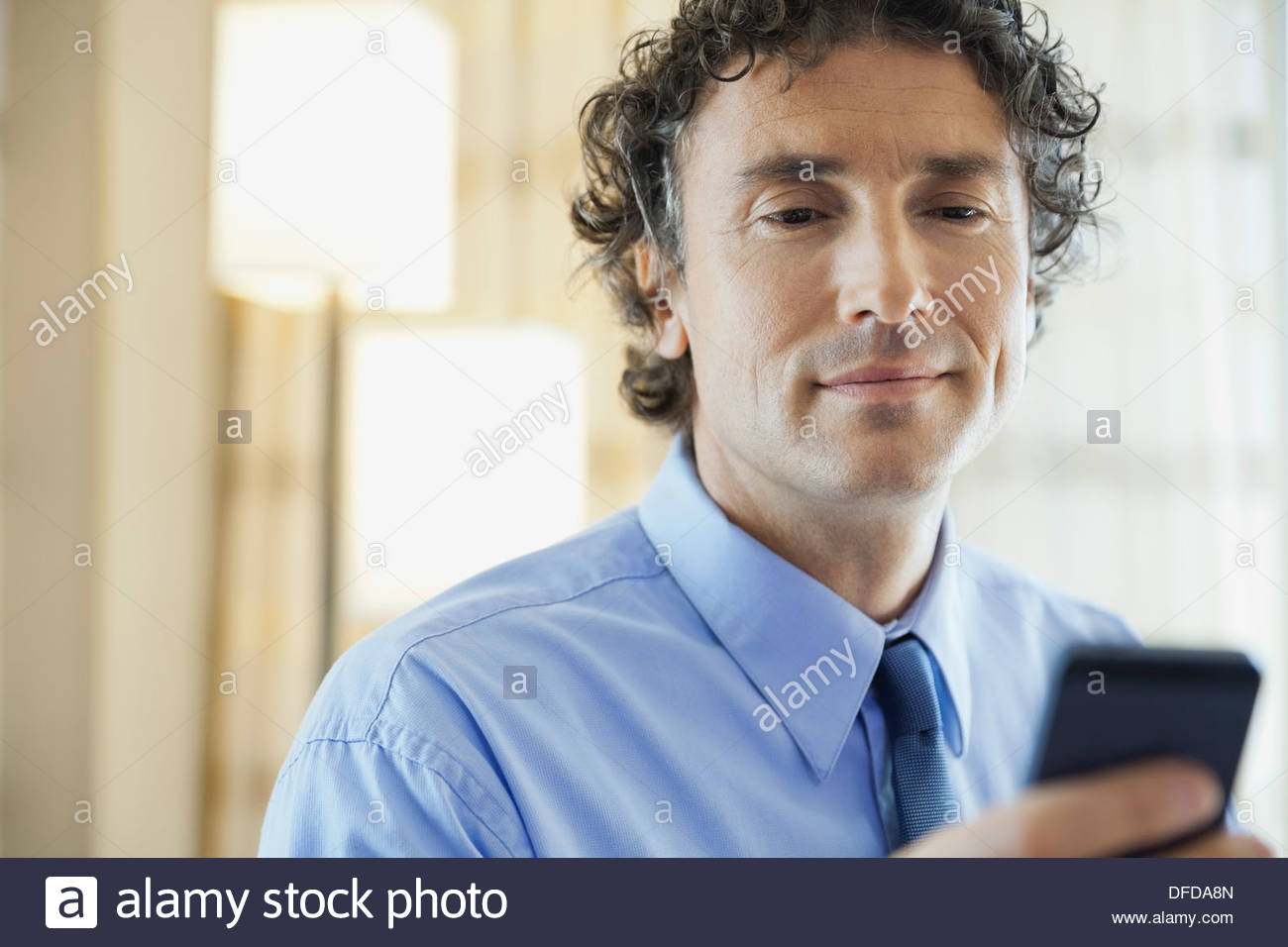 Businessman text messaging in hotel room - Stock Image