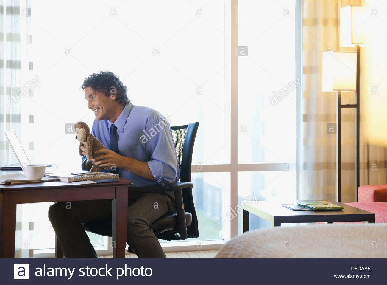 Man in hotel room on business trip video chatting with kids at home - Stock Image