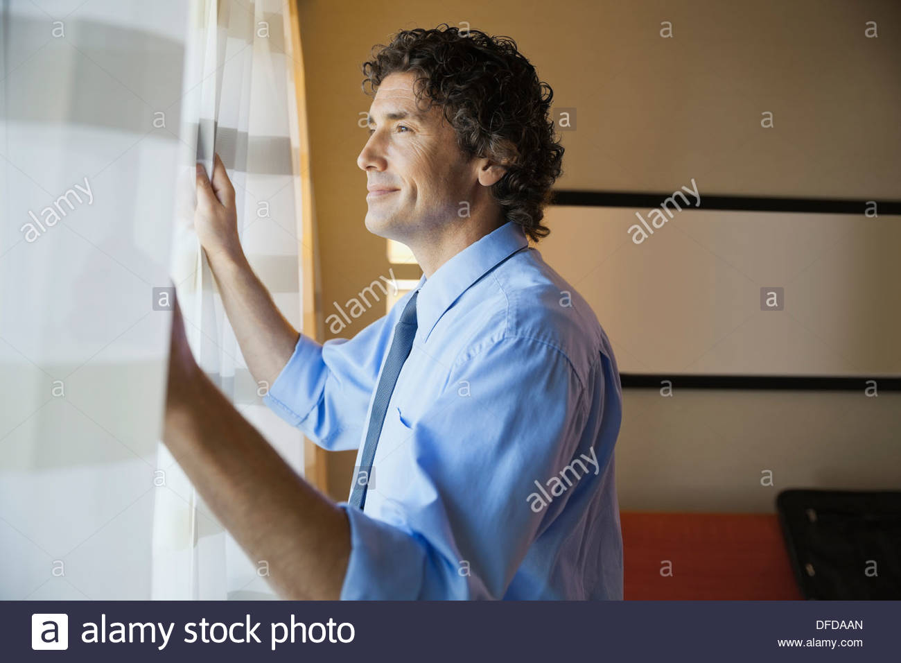 Smiling businessman looking out window in hotel room - Stock Image