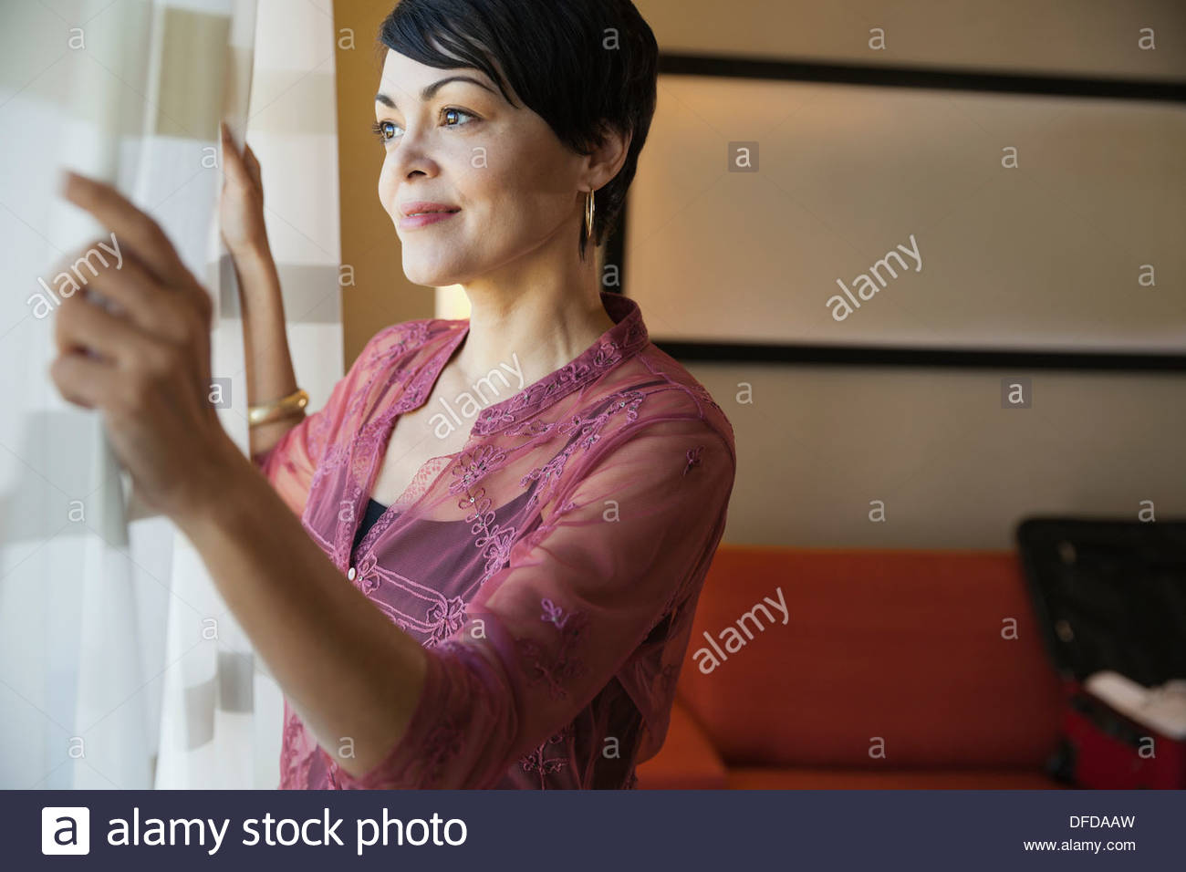 Businesswoman looking out hotel room window - Stock Image
