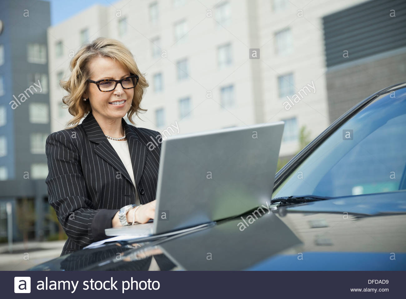 Businesswoman using laptop on car hood outdoors - Stock Image