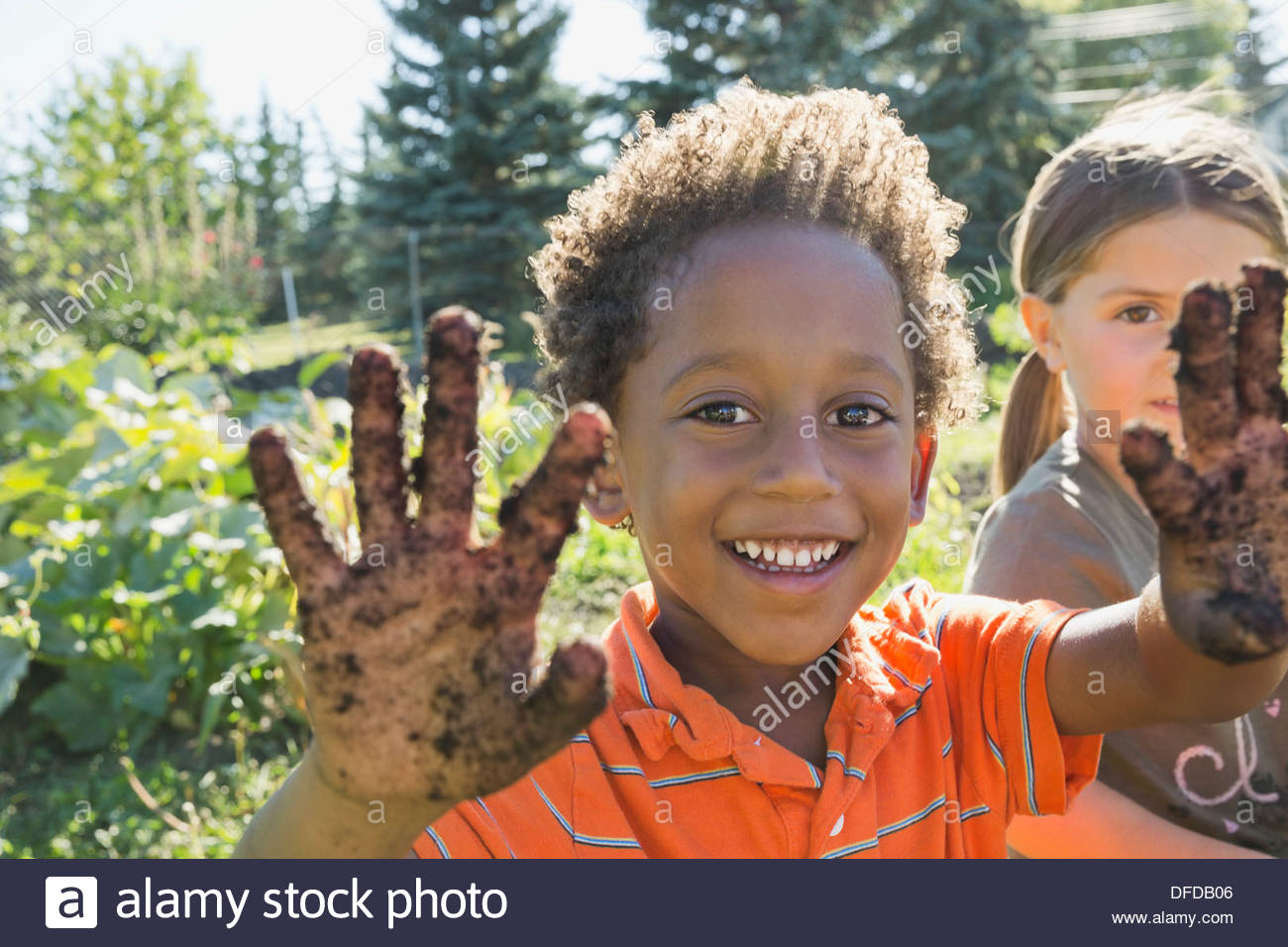 Portrait of boy showing hands covered in dirt - Stock Image