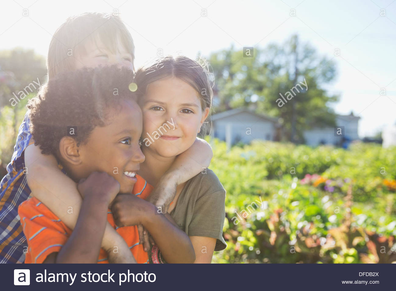 Portrait of cute girl with friends in community garden - Stock Image